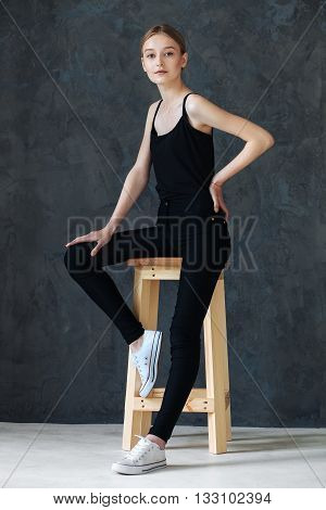 Young European woman posing in studio for test photo shoot showing different poses sitting on bar stool