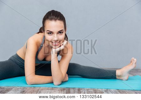 Young smiling healthy fitness woman doing splits isolated on grey background