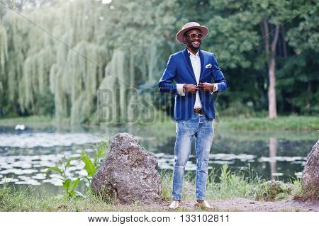 Stylish Smiled African American Man At Blue Jacket, Sunglasses And Hat