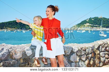 Happy Mother And Child Pointing Into Distance In Front Of Lagoon