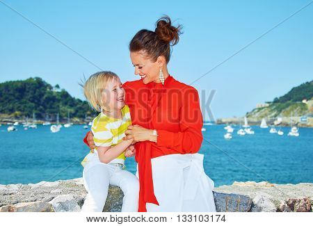 Happy Mother Playing With Child In Front Of Lagoon With Yachts