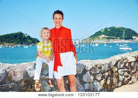 Portrait Of Smiling Mother And Daughter In Front Of Lagoon