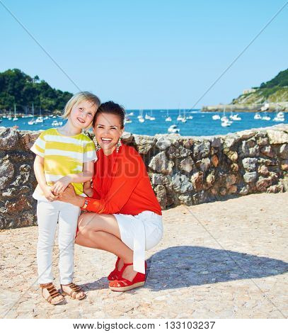 Happy Mother And Daughter In Front Of Lagoon With Yachts