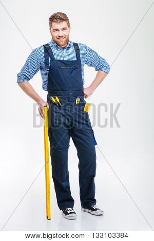 Full length portrait of a happy male builder standing isolated on a white background