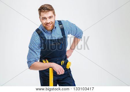Handsome male builder standing with equipment isolated on a white backgound