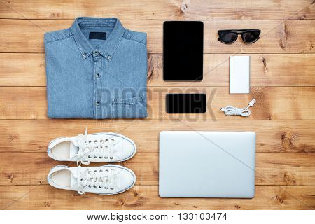 Travel concept shoes, shirt, mobile phone, laptop,mp3, usb, eyeglasses, tablet on the desk