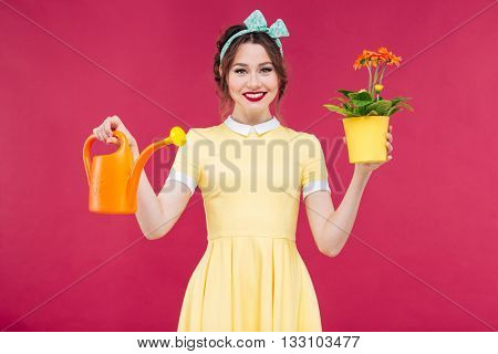 Smiling lovely pinup girl holding flowers in pot and orange watering can over pink background