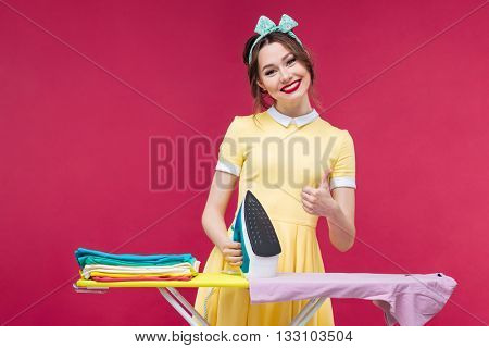 Happy lovely pinup girl ironing clothes and showing thumbs up over pink background