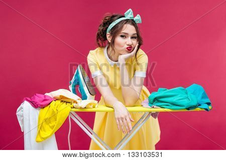 Bored sad young woman ironing clothes over pink background