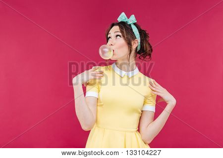 Thoughtful attractive young woman blowing bubble from chewing gum over pink background