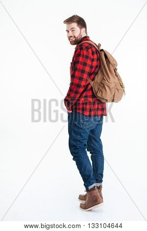 Full length portrait of a casual man looking back at camera isolated on a white background