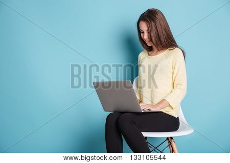 Young beautiful smart woman using laptop pc computer for study isolated on the blue background