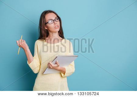 Young smart pensive girl thinking about something and holding colorful binders isolated on the blue background