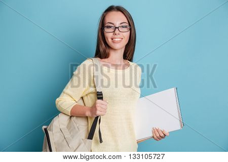 Beautiful young girl with bagpack and notebook isolated on the blue background
