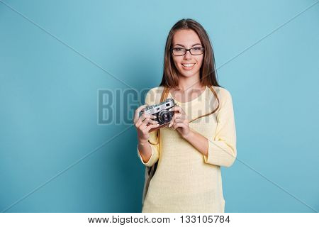 Cheerful young woman with photo camera isolated on the blue background