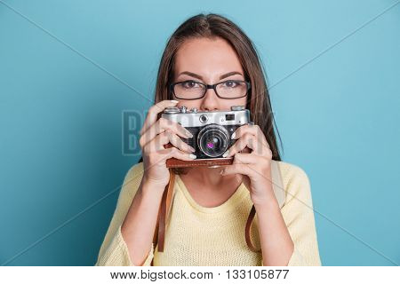 Beautiful young pretty woman with photo camera isolated on the blue background