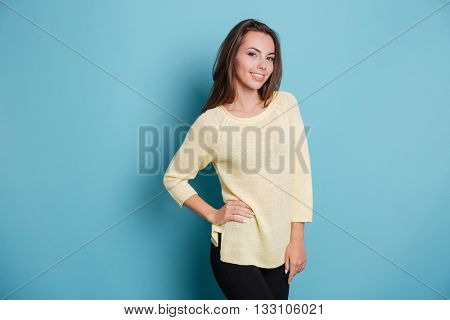 Beautiful young brunette girl holding her hand on hips isolated on the blue background