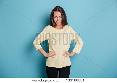 Beautiful condident young girl looking at camera and holding arms on her hips isolated on the blue background