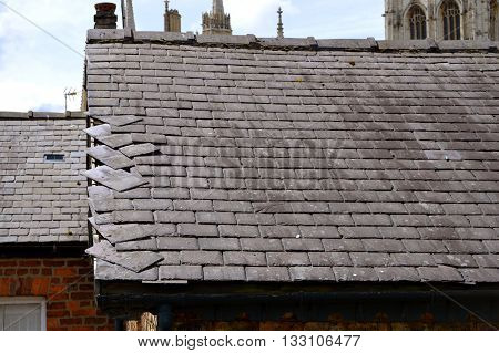 Loose slates on a storm damaged house roof