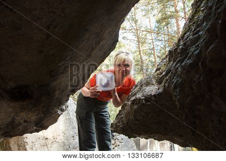 A female geocacher with a geocache container in a forest