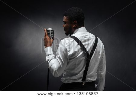 Back view portrait of afro american man singing into vintage microphone over dark background