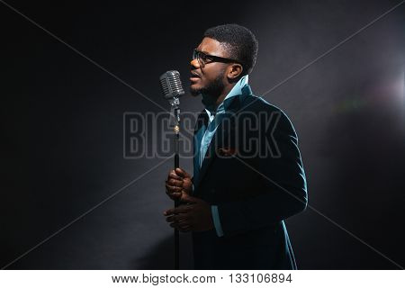 Afro american man singing into vintage microphone over dark background