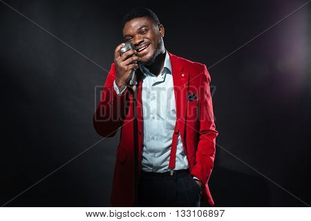 Stylish afro american man singing into vintage microphone over dark background