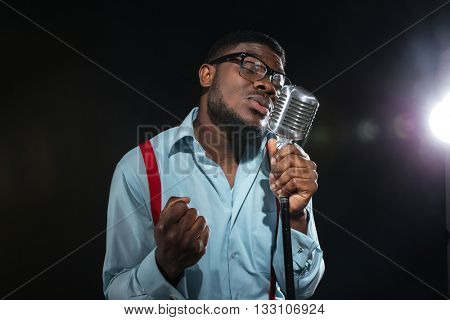 Handsome afro american man singing into vintage microphone over dark background