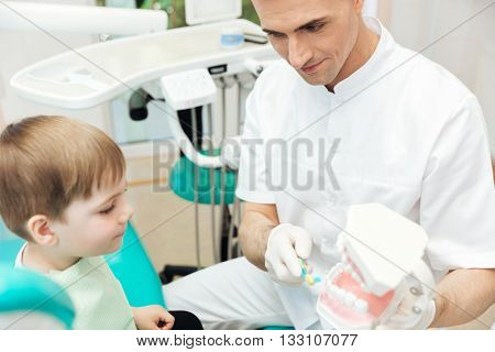Dentist showing how to brush teeth and use toothbrush using dental jaw model