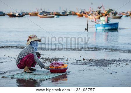 Woman sitting on the beach, Mui Ne, Vietnam