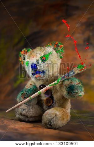 Painted furry bear toy holding a bursting red paint paintbrush