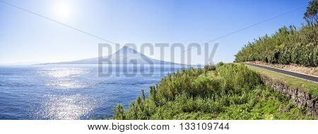 asphalted road in Azores runs along the grassy shores of the Atlantic Ocean on a background of of an extinct volcano and the blue sky