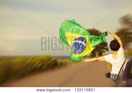 Woman holding Brazil flag - Sport fans traveling to Rio de Janeiro