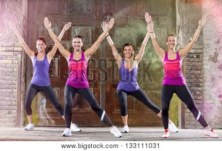Young group of woman in colorful athletic shirts keep fit shape exercising outdoor
