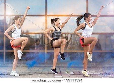 Three athletic girls doing aerobic exercises outside
