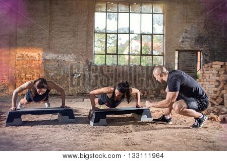 Coach trains young girls exercising push-ups in deserted building