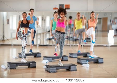 Exercisers in colorful sportwears with young curly female instructor on group training