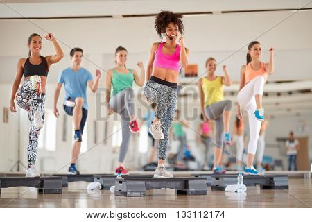 Young group of people exercising on stepper at gym
