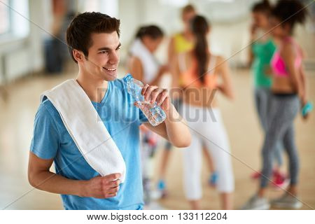 Thirsty guy drinking water from bottle after training in gym