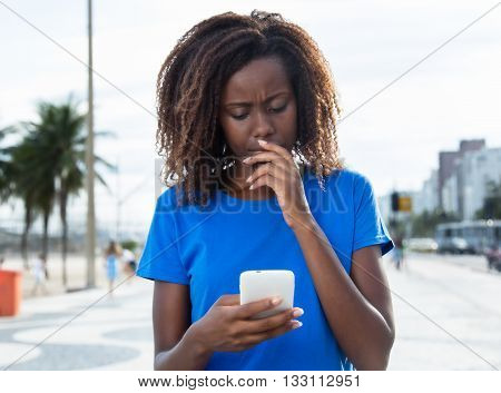 Thinking african woman in a blue shirt with phone outdoor in the city