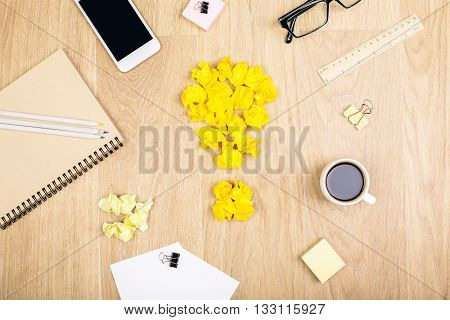 Top view of wooden desktop with crumpled yellow paper lightbulb coffee smartphone and various stationery items. Idea concept