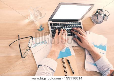 Male hands using blank white laptop on office desk with business report glass of water and alarm clock. Mock up