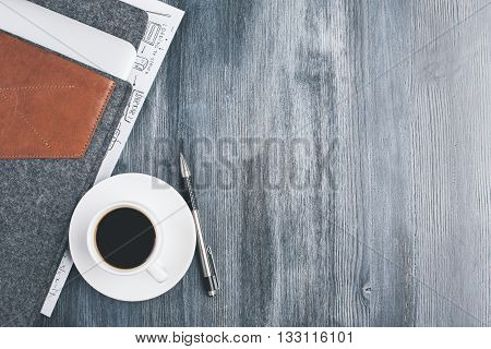 Top view of dark wooden desktop with coffee cup and saucer pen and notebook cover. Mock up