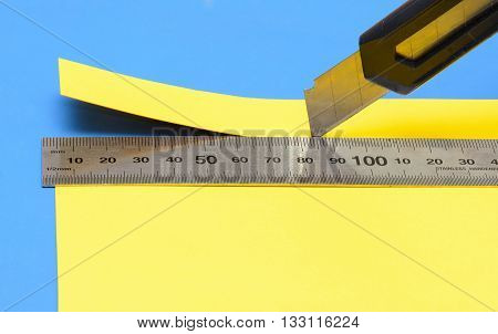 cuts off a piece of yellow paper with a knife and a  stainless steel ruler on blue cutting mat