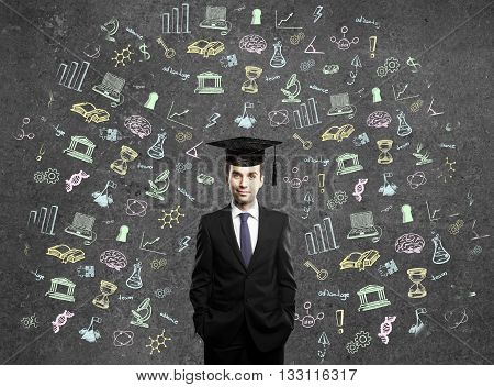 Graduation concept with education related sketches around businessman in cap on dark concrete wall background