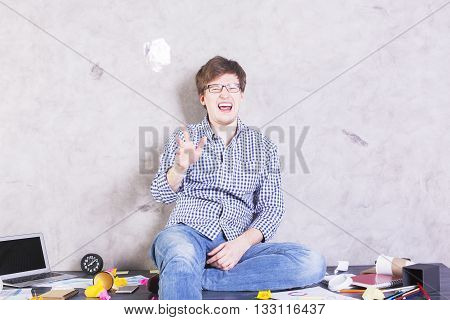 Crazy caucasian man sitting on messy office desktop with concrete wall in the background