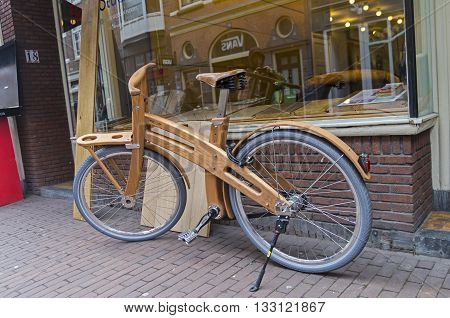 AMSTERDAM THE NETHERLANDS - APRIL 10 2013: Wooden bicycle on the streets of Amsterdam Holland. It seems to be quite a workable bike not just a curious thing.