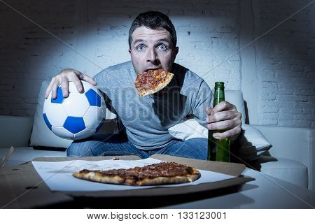 crazy football fan man watching soccer game on television at home sofa couch with soccer ball and pizza in his mouth holding beer bottle looking anxious nervous and suffering stress