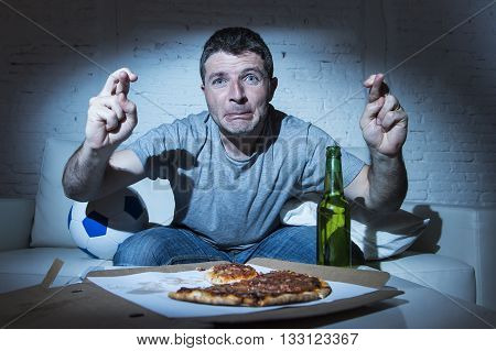 young man watching football game on television nervous and excited suffering stress crossing fingers for goal on sofa couch at home with ball beer bottle and pizza looking crazy anxious