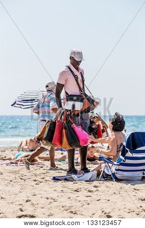 Alikante, Spain- June 4, 2016: An illegal immigrant, negro, from Africa sells fake bags on the beach in Spain